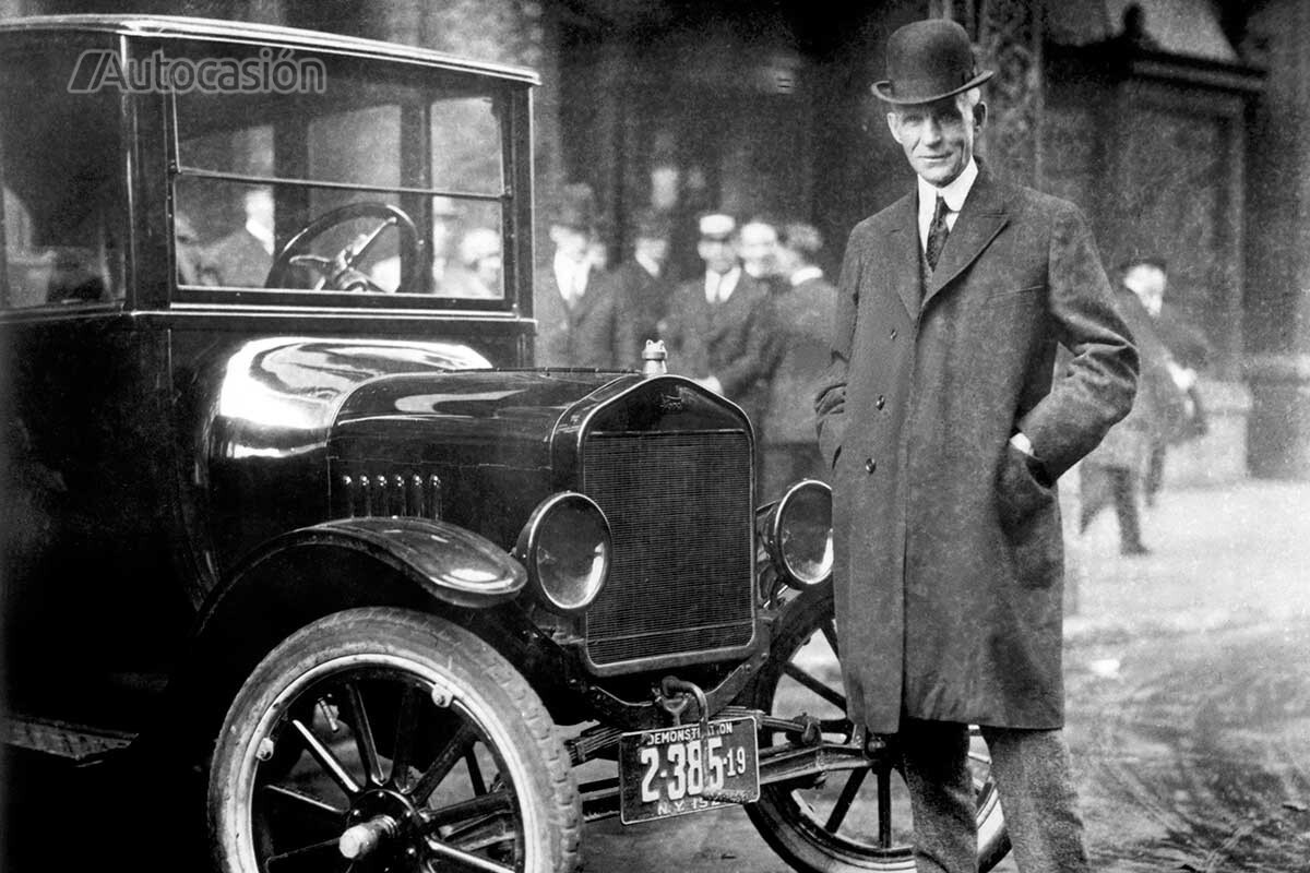 Henry Ford next to one of the first windshields on a car